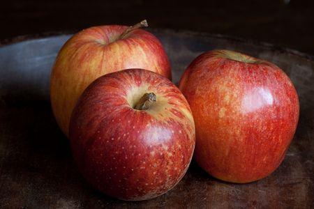 three fresh red apples on dark wooden background