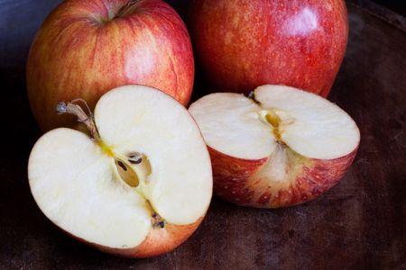 Three apples one cut open on dark background