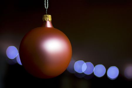 Pink christmas ball over black background and lights