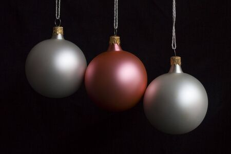 White and pink christmas balls over black background