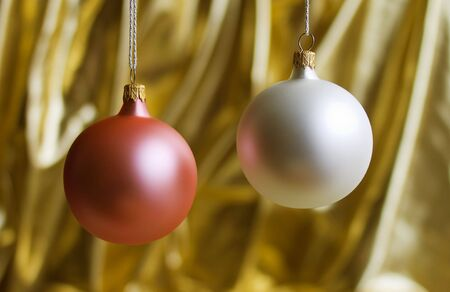 White and pink christmas balls over golden background