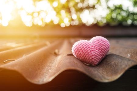 zinc: Pink heart knitting on roof in mornig sun.