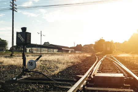 Railroad switch with train in the morning sun. Stock Photo