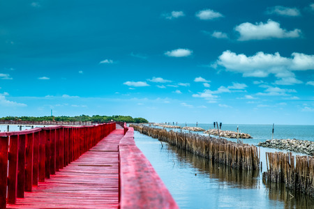 Red bridge and bamboo line slow down wave prevent coastal erosion. Stock Photo