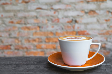 Cappuccino coffee in white cup on wooden table with old brick wall background