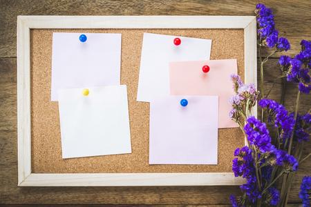 Leere Notizen auf der Korkplatte mit trockenem Blumenstrauß, hölzernem Hintergrund.
