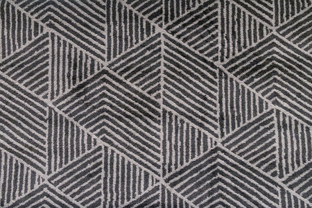 Black and grey carpet with hand made geometric pattern.
