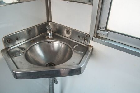 Stainless steel sink in the corner on the train.