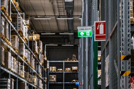 Emergency exit route and Extinguisher sign on top of warehouse.