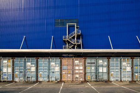 View of many shipping containers doors with fire escape blue background.