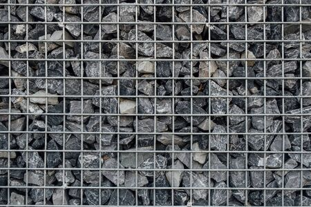 Wall made of natural stone and metal mesh for construction. Reklamní fotografie