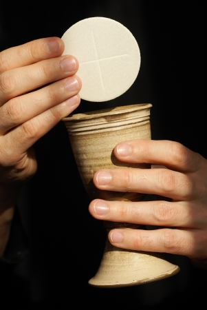 communion wafer: Hands with chalice and communion wafers on black background Stock Photo