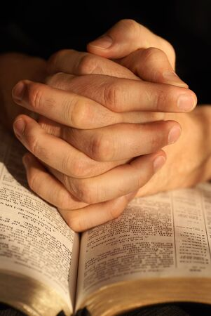 Detail of the Holy Bible opened on Psalm 23 and  hands in prayer photo