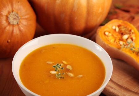Bowl with pumpkin soup, baked butternut squash and pumpkins photo