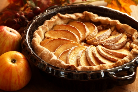 Arrangement of home-made apple pie and apples.