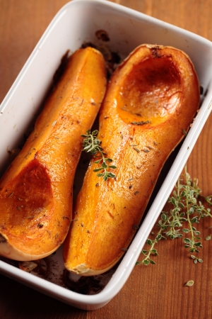 butternut: Tray with baked butternut squash and herbs.