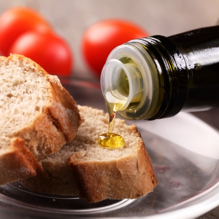 cooking oil: Close-up of olive oil pouring on slices of bread. Stock Photo