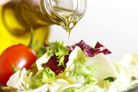 foglie ulivo: Close-up della bottiglia con versando insalata di olio d'oliva e verdura Archivio Fotografico