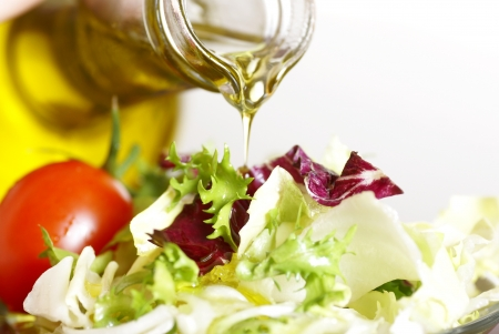 cooking oil: Close-up of bottle with pouring olive oil and vegetable salad