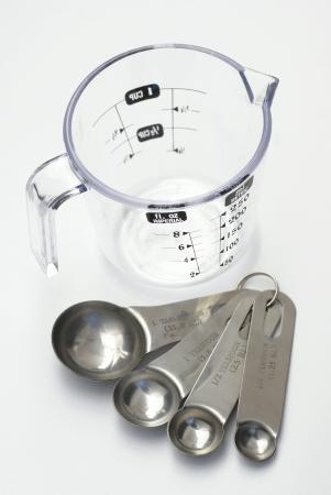 흰색 배경에 컵과 숟가락을 측정합니다.