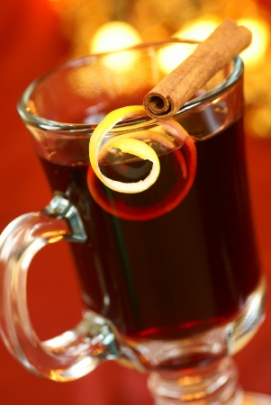 mulled wine spice: Mulled wine with lemon peel and cinnamone stick on glass. Selective focus, shallow DOF. Stock Photo