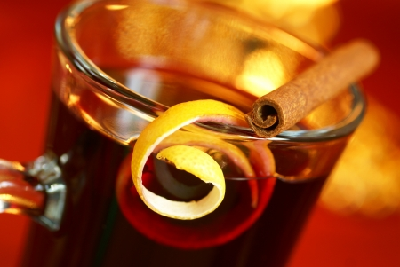 Mulled wine with lemon peel and cinnamone stick on glass. Selective focus, shallow DOF. Stock Photo