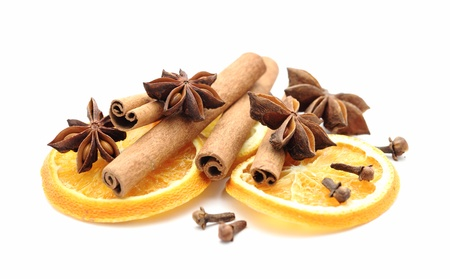 Dry orange slices, cinnamon sticks, anise and clove on white background