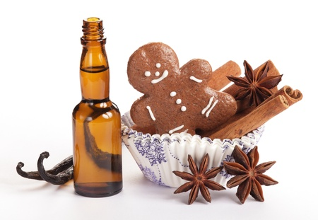 Close-up of gingerbread man, vanilla beans, anise stars, cinnamon sticks in paper cupcakes and baking extract in a bottle on white background Stock Photo - 20868866