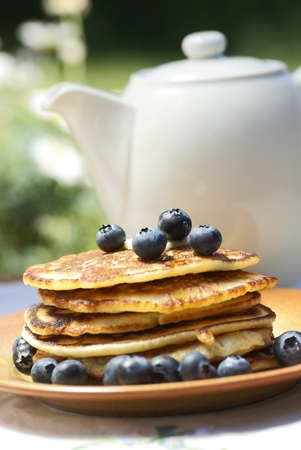 Stack of pancakes with blueberries and jug photo