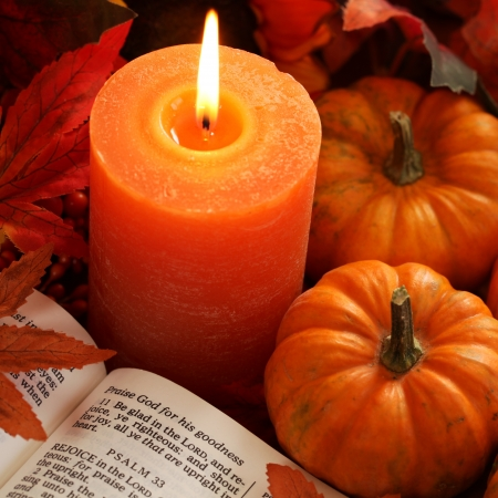 autumn arrangement: Open Bible, candle, and autumn decorations.