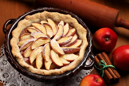 Apple pie in baking tin, cinnamon sticks and apples Stock Photo