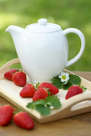 Jug with tea or coffee and strawberries photo