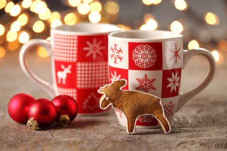 gingerbread cookie: Mugs with hot drink and gingerbread cookie.