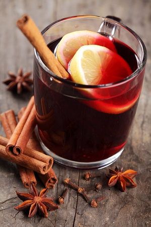 Mulled wine and spices on wooden background