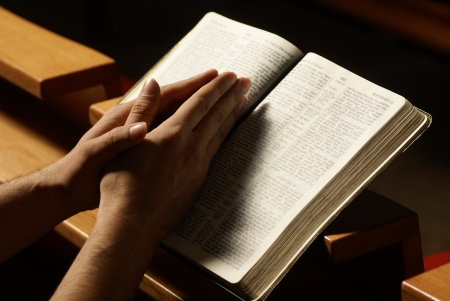 Hands on Holy Bible in prayer at church Stock Photo - 20902400