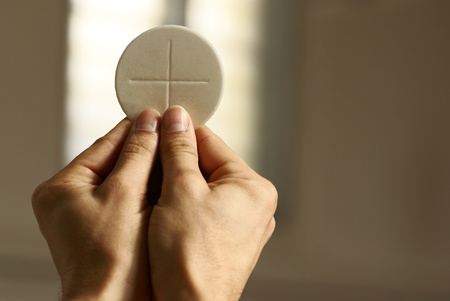 Hands holding communion wafer at church interior