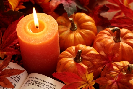 Open Bible, candle, and autumn decorations
