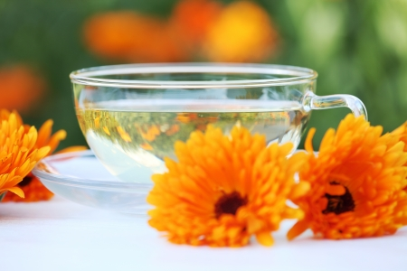 Cup with marigold (calendula) tea and marigold flowers on a table photo