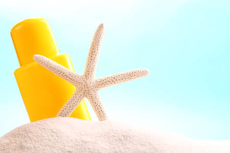 sun lotion: Sun lotion and starfish on sand  Stock Photo