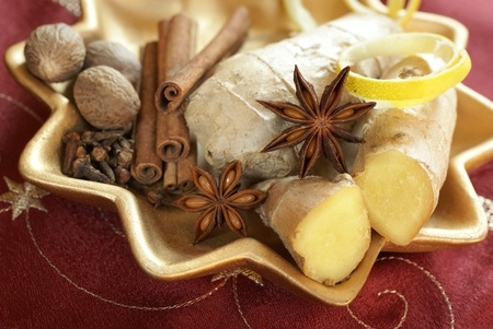 Decorative plate with ginger, lemon peel, anise, clove, nutmeg and cinnamone sticks. Stock Photo