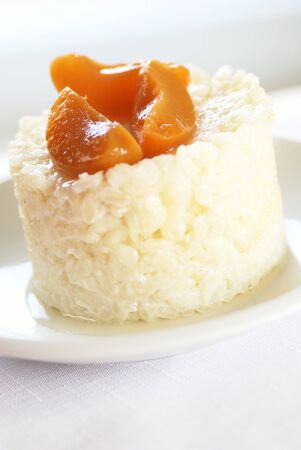 Sweet rice pudding with apricots on white plate
