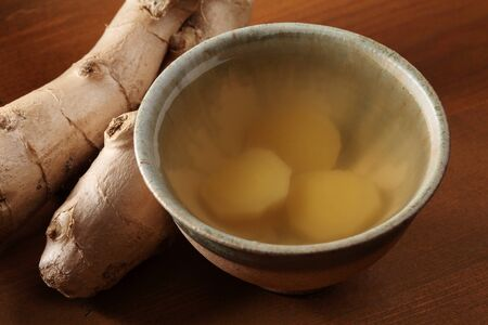 Cup of ginger tea and fresh ginger.  photo