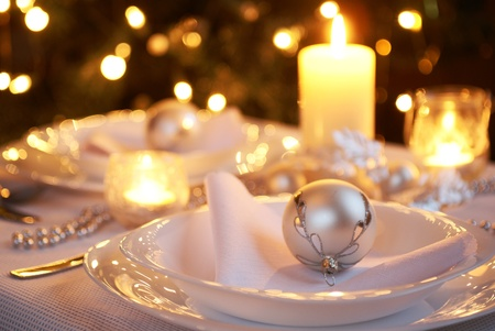 Table setting with Christmas decorations and Christmas tree in a background  photo