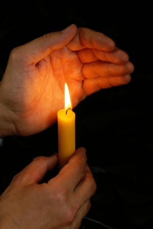 Hand with burning candle  Black background with copy space