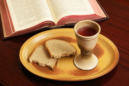 Chalice, bread and open Bible on a table