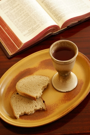 Chalice, bread and open Bible on a table  photo