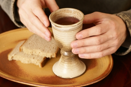 Hands with chalice and bread photo