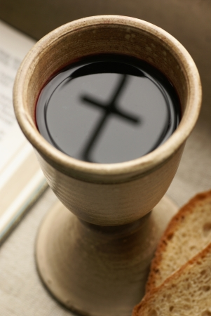 Chalice with wine, piece of bread and open Bible  Stock Photo
