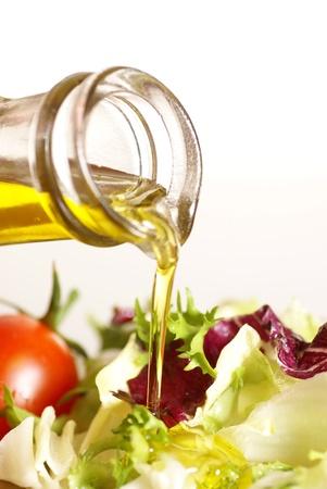 オリーブ オイルを注ぐと野菜のサラダとボトルのクローズ アップ 写真素材