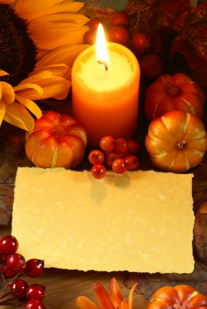 Arrangement of sunflower, candle and autumn decorations on wooden background with paper copy space. Stock Photo